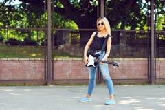 太阳镜的美丽的行家女孩有电吉他的 免版税库存图片