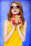 太阳镜的美国红头发人女孩与礼品。 免版税图库摄影