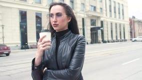 太阳镜的美女 站立在街道上,调查距离和饮用的咖啡从一纸杯 强的wi 影视素材