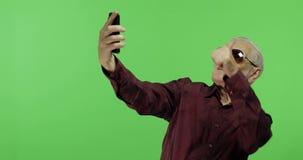 太阳镜的老人游人在智能手机做一张照片 Selfie 股票录像