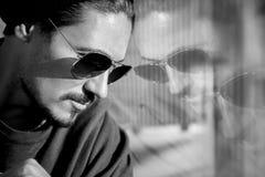 太阳镜的英俊的人在一个大城市的街道上 反射 北京,中国黑白照片 库存图片