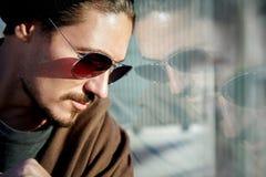 太阳镜的英俊的人在一个大城市的街道上 反射 免版税库存照片