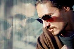 太阳镜的英俊的人在一个大城市的街道上 反射 库存图片