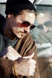 太阳镜的英俊的人在一个大城市的街道上 反射 库存照片