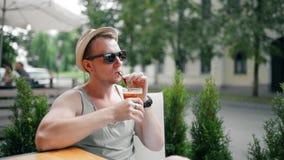 太阳镜的英俊的人微笑和饮料鸡尾酒并且放松 影视素材
