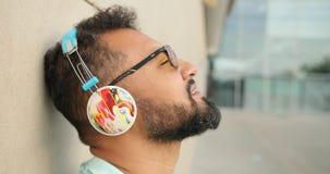 太阳镜的英俊的非洲人享受在耳机的转动的观点的音乐 4k英尺长度 影视素材