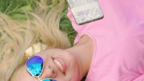 太阳镜的说谎在草的,在智能手机的观看的图片微笑的女孩 股票视频
