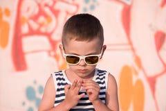 太阳镜的逗人喜爱的小男孩拔出从他的手指的一块裂片 免版税图库摄影
