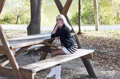 太阳镜的金发碧眼的女人在湖的一张木桌上 库存照片