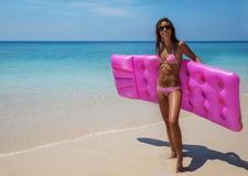 太阳镜的年轻亭亭玉立的深色的妇女在热带海滩晒日光浴 库存图片