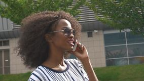太阳镜的年轻可爱的非裔美国人的女商人谈话在手机和微笑 影视素材