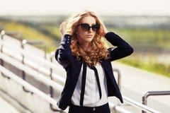 太阳镜的年轻时装业妇女走在城市街道上的 库存照片
