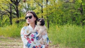 太阳镜的年轻时髦的妇女走在有哈巴狗品种狗的公园的  拿着在他的胳膊的一只宠物 影视素材