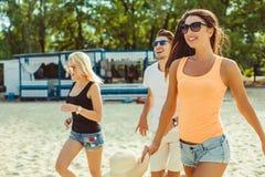 太阳镜的年轻滑稽的人在海滩 一起朋友 免版税库存图片