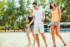 太阳镜的年轻滑稽的人在海滩 一起朋友 免版税图库摄影