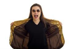 太阳镜的年轻滑稽的魅力夫人打开了她的嘴和拿着手夹克 库存图片