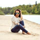太阳镜的年轻美丽的妇女坐海滩 免版税库存图片