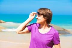 太阳镜的年轻英俊的人微笑对海滩的 免版税库存照片