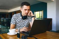太阳镜的年轻英俊的行家人在自助食堂使用膝上型计算机 免版税库存照片