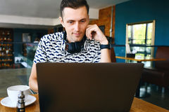 太阳镜的年轻英俊的行家人在自助食堂使用膝上型计算机 免版税图库摄影
