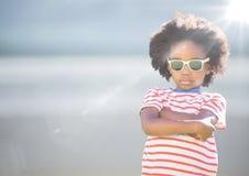 太阳镜胳膊的男孩折叠了反对与火光的模糊的海滩 图库摄影