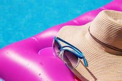 太阳镜草帽桃红色气垫游泳池 热带概念 库存照片