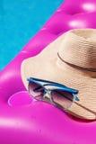 太阳镜草帽桃红色气垫游泳池 热带概念 免版税库存照片