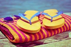 太阳镜,啪嗒啪嗒的响声和海滩毛巾,在一条木木板走道 库存图片