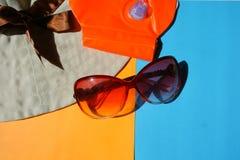 太阳防护玻璃,在蓝色和橙色背景的帽子 免版税库存照片