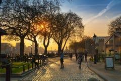 太阳集合的塔公园 与休息由水的人的泰晤士河人行道 伦敦 库存图片