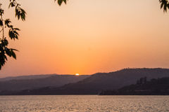 太阳去的downSunsets太阳淡桔色的颜色山 库存图片