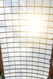 太阳` s光芒通过购物中心的玻璃屋顶发光 美好的现代建筑背景 蓝色多云天空和 库存图片