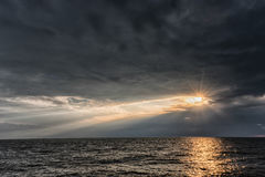 太阳` s发出光线穿过暴风云在海 接近利耶帕亚 拉脱维亚 库存图片