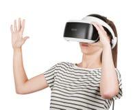 夫人使用一个虚拟现实耳机,隔绝在白色背景 新的音响器材 虚拟现实风镜的一个女孩 库存图片