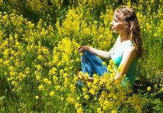 夫人参与凝思在黄色花中的一个城市公园 做瑜伽凝思的美丽的妇女在公园 免版税图库摄影