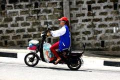 夫人在一条艰难路骑她的e自行车或电子自行车在安蒂波洛市 免版税库存图片