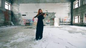 夫人在一间搁浅的屋子穿礼服并且弹小提琴 股票录像