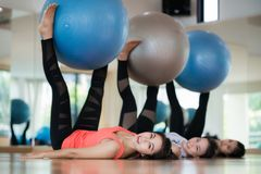 夫人在健身中心,有氧运动采取球锻炼与球gr 免版税库存照片