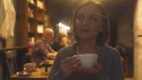 夫人在她的在咖啡馆和饮用的软的风味热奶咖啡的40s消费晚上 影视素材