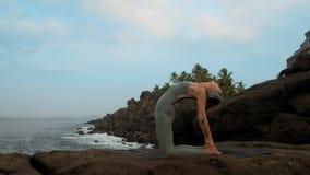 夫人在岩石海洋海滩慢动作的骆驼姿势站立 股票录像