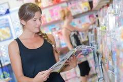 夫人在报刊经销人的浏览杂志 库存照片