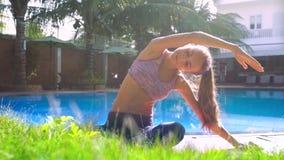 夫人在瑜伽姿势弯曲的手上思考到左边由水池 股票录像