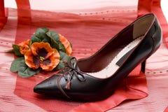 夫人在红色布料穿上鞋子 免版税图库摄影
