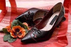 夫人在红色布料穿上鞋子 免版税库存照片