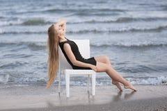 夫人坐在海滩的一把椅子 有长的头发的一个俏丽的女孩在一件黑礼服 蓝色海洋背景的一个平安的夫人 库存图片