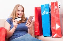 夫人坐拿着智能手机的长沙发显示信用卡 免版税库存图片