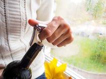夫人坐窗台打开一个瓶与拔塞螺旋的酒 库存图片