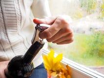 夫人坐窗台打开一个瓶与拔塞螺旋的酒 库存照片