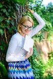 夫人快乐的笑她喜欢滑稽可笑的故事 女孩敏锐对书继续读 放松在公园的妇女白肤金发的作为断裂 库存图片
