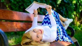 夫人愉快的面孔喜欢读 女孩放置放松与书,绿色自然背景的长凳公园 妇女花费休闲与 免版税图库摄影